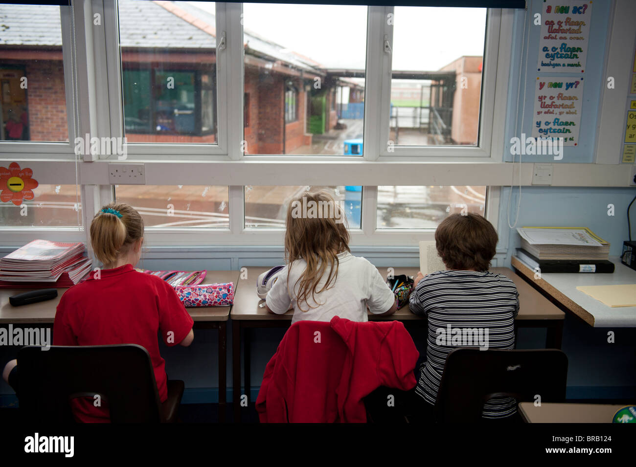 Rear view of three Primary school children sitting at their desk, UK - Stock Image