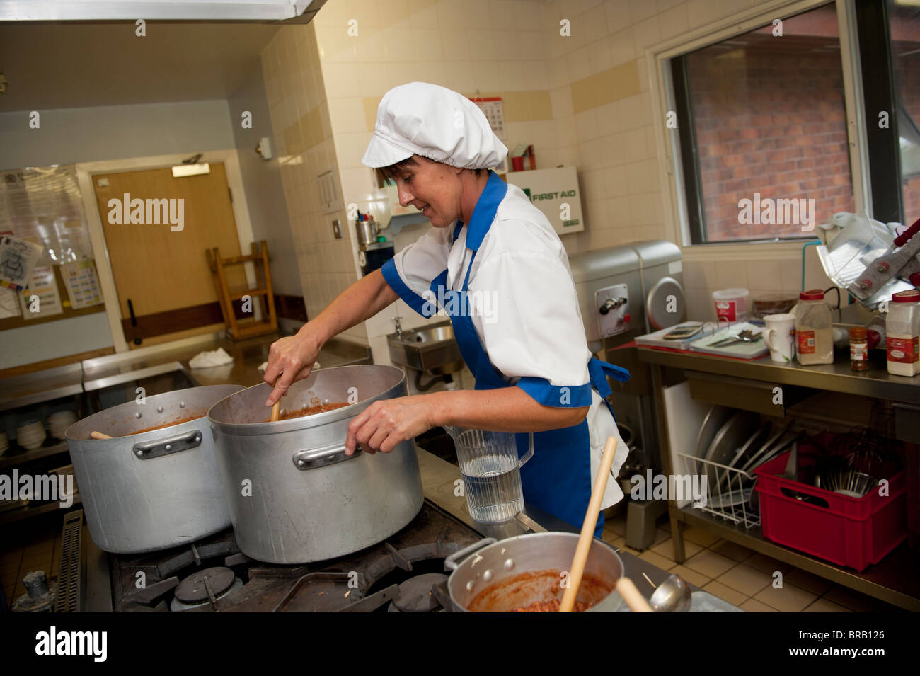 School cook preparing dinner in a primary school kitchen, UK - Stock Image