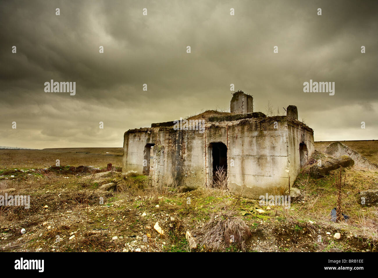 Landscape with a decrepit ruin of a building under moody sky - Stock Image