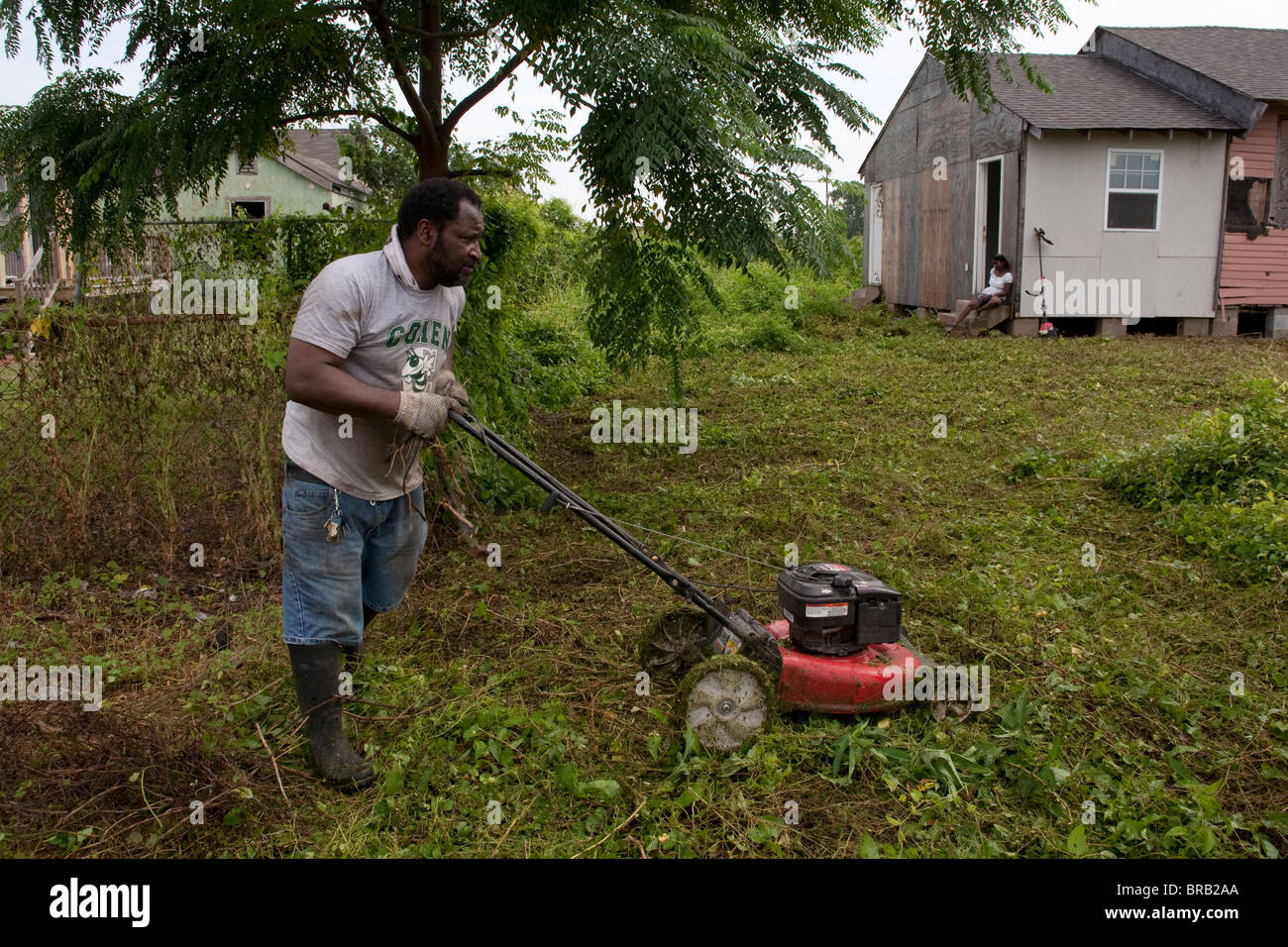 A man cuts weeds from the from yard of his partially rebuilt home in New Orleans, Louisiana's Ninth Ward. - Stock Image