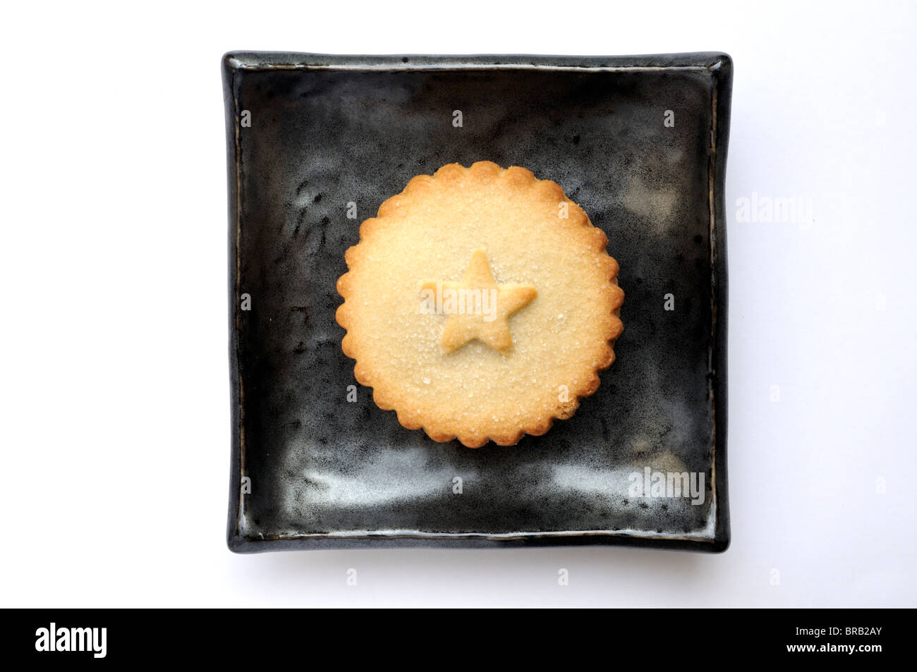 One Christmas mince pie on black square plate. - Stock Image