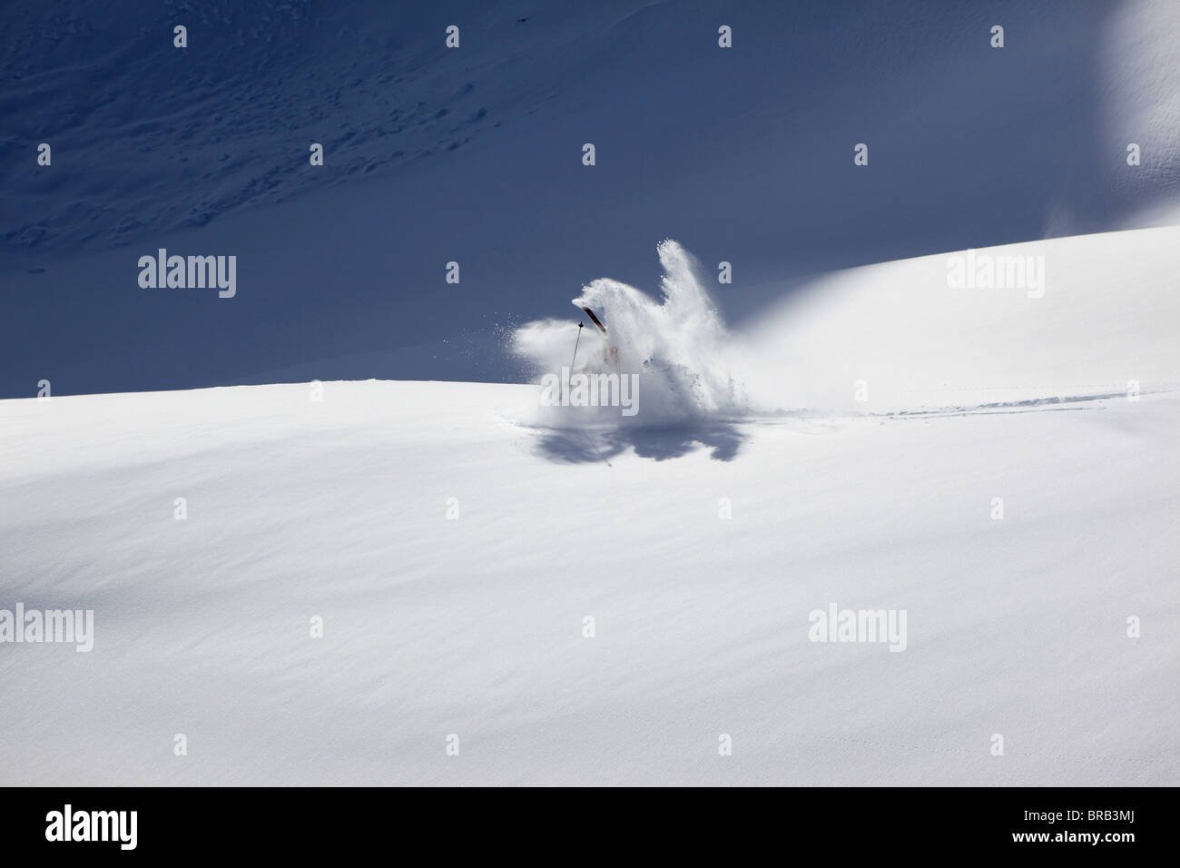 A skier falls after a jump in deep powder on a Val Gardena off piste slope - Stock Image
