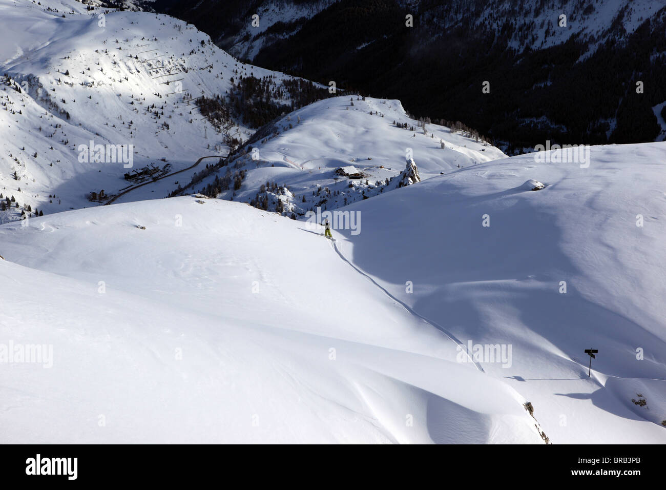 A female snowbarder enjoys a powder day and draws a lonely line on a Val Gardena off piste slope - Stock Image