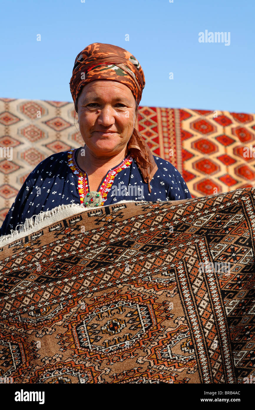 Turkmenistan - Ashgabat - woman displays a carpet at the Sunday Market - Stock Image