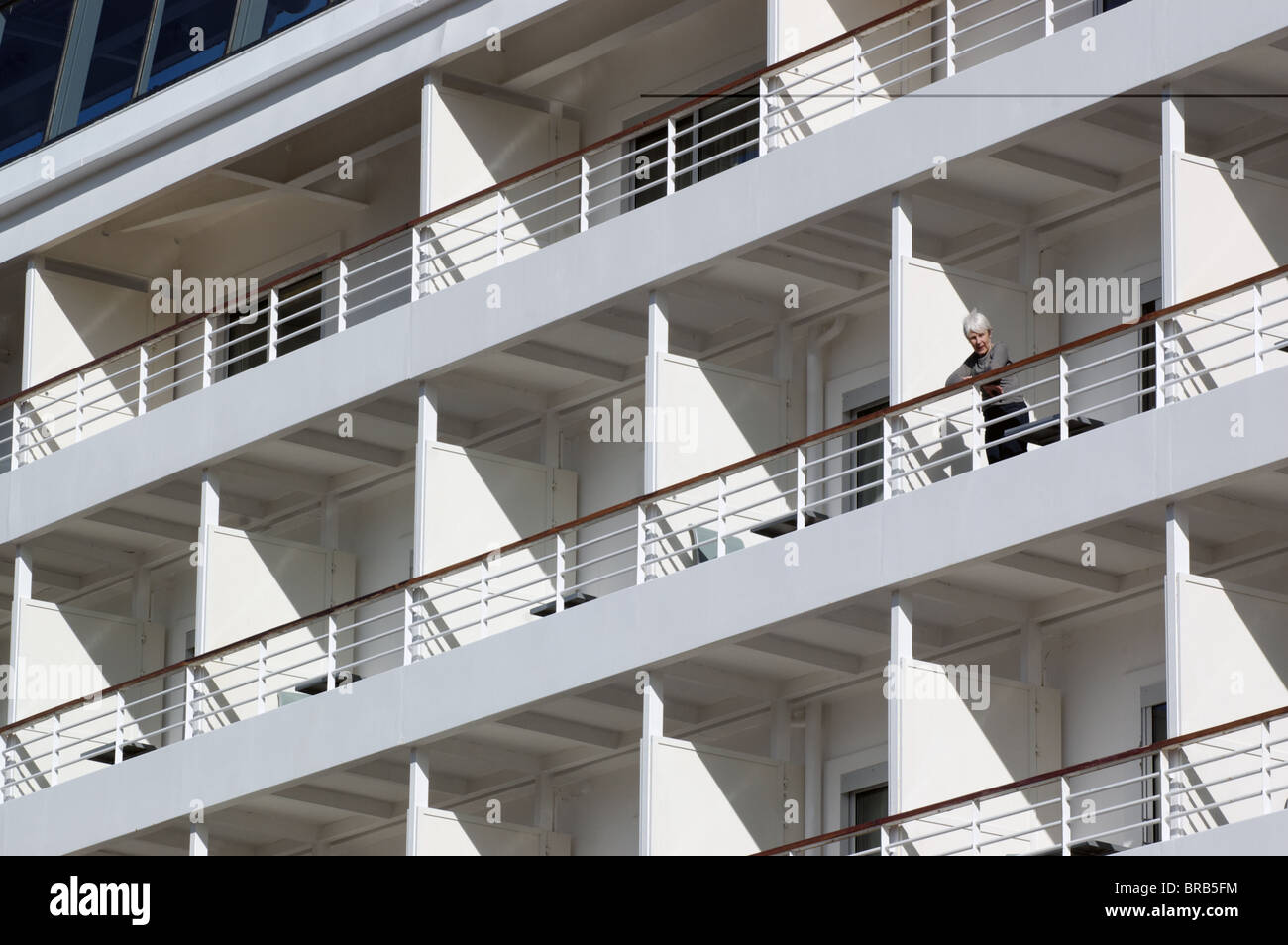 The cabins of a cruise ship with a woman looking down at the harbour - Stock Image