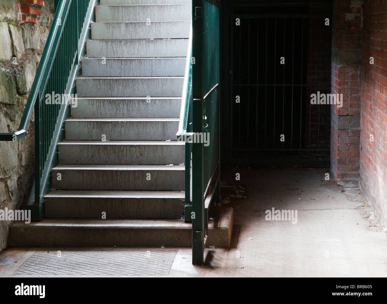 Green railing City Cellar Stairs leading down to stone and brick lower level - Stock Image