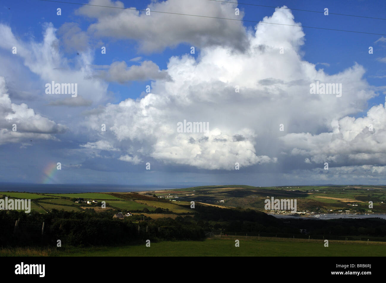 Rainbow and cumulonimbus cloud over Cardigan Bay, St Dogmaels, Pembrokeshire, Wales, United Kingdom - Stock Image