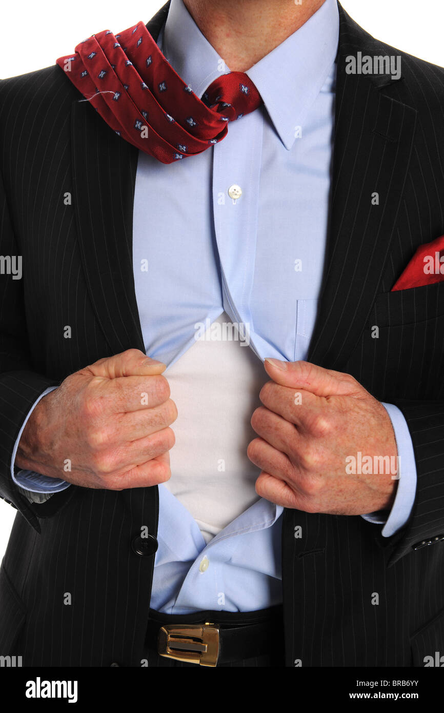 Torso of businessman opening shirt to reveal t-shirt - Stock Image