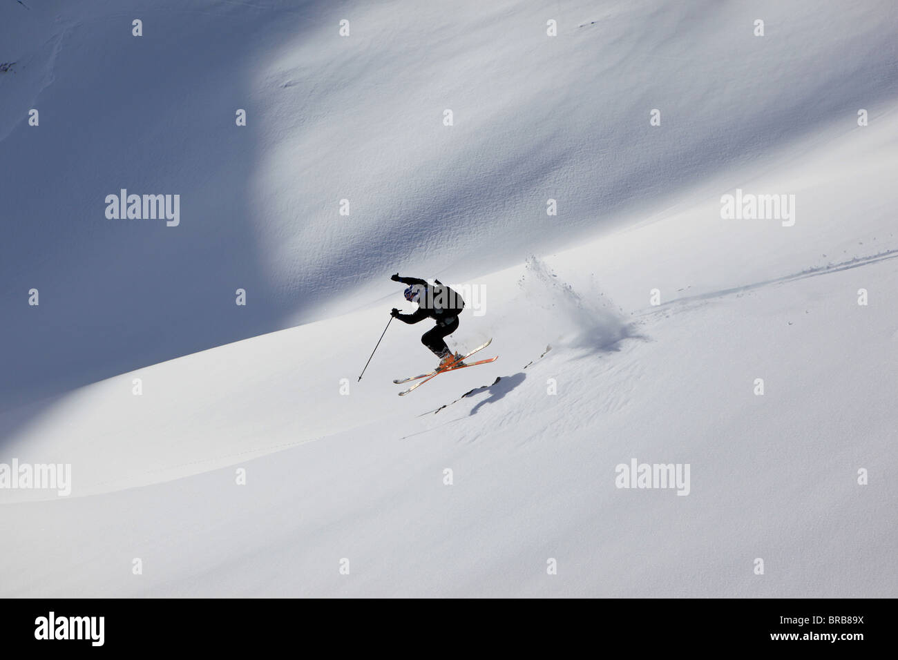A skier jumps over some rocks into the powder on a Val Gardena off piste slope - Stock Image