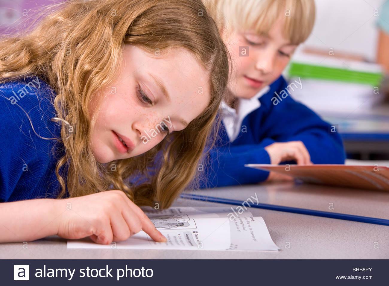 School girl reading workbook in classroom - Stock Image