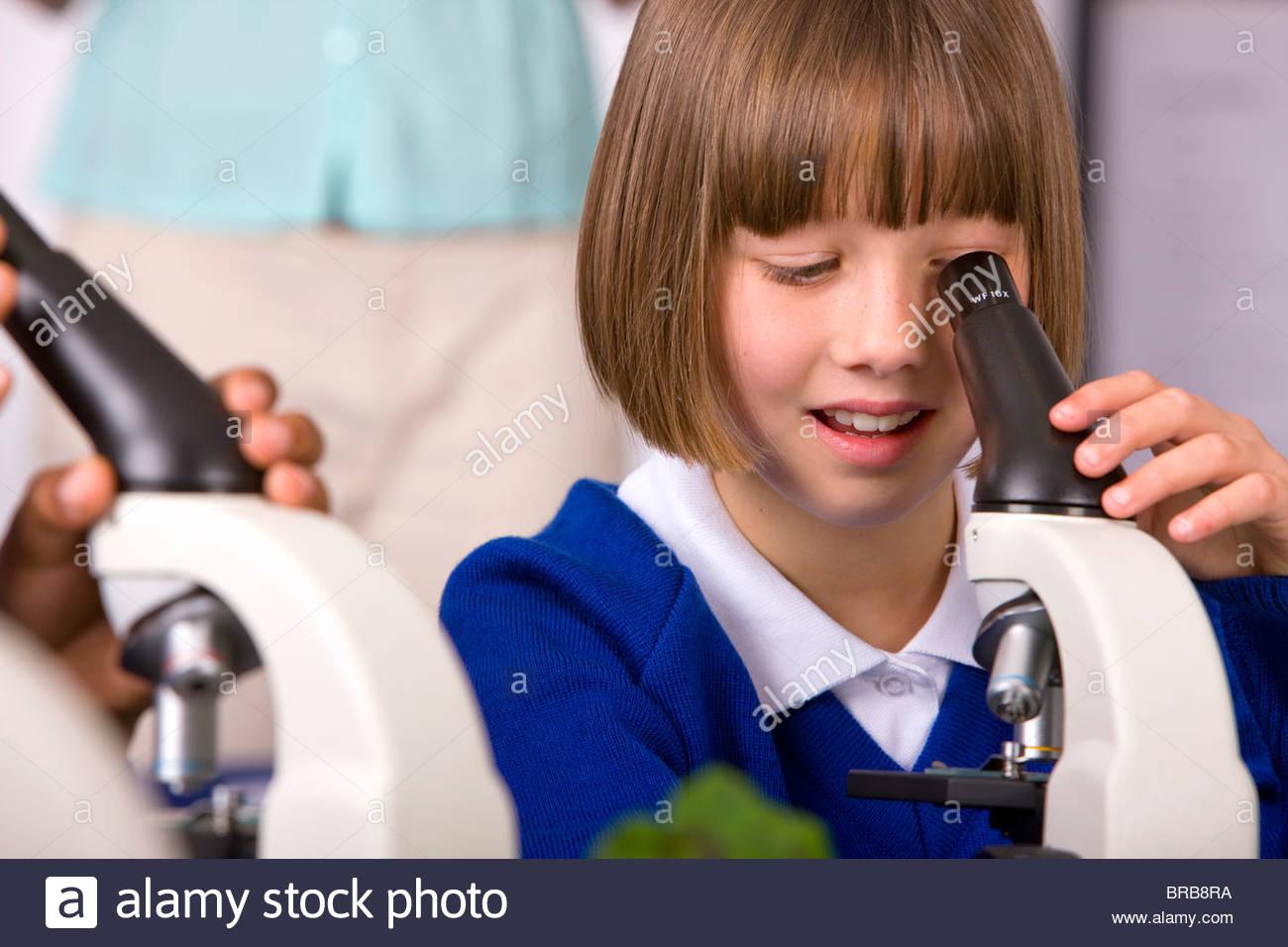 School children looking into microscopes in classroom laboratory - Stock Image