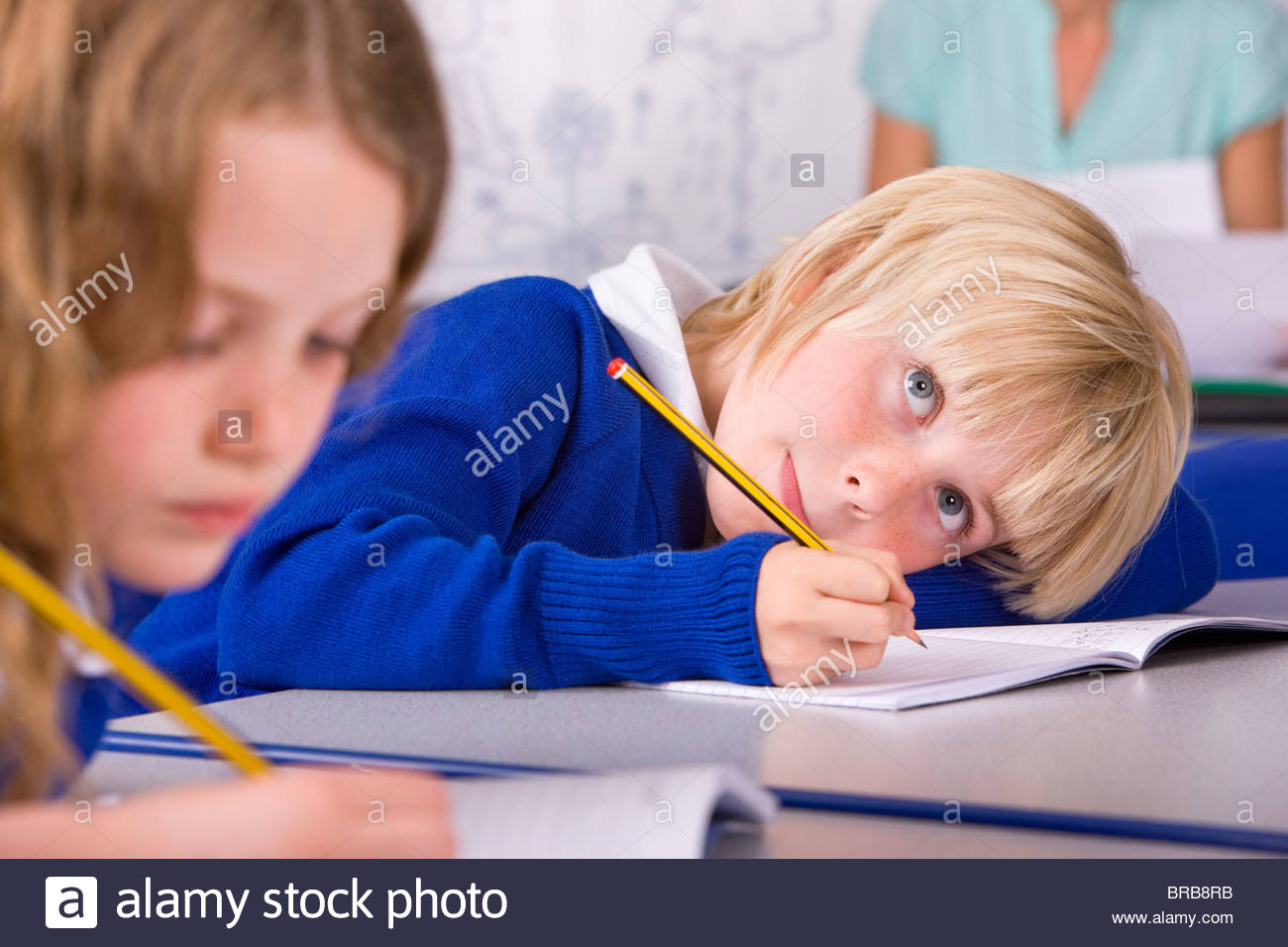 School boy thinking and writing in workbook - Stock Image