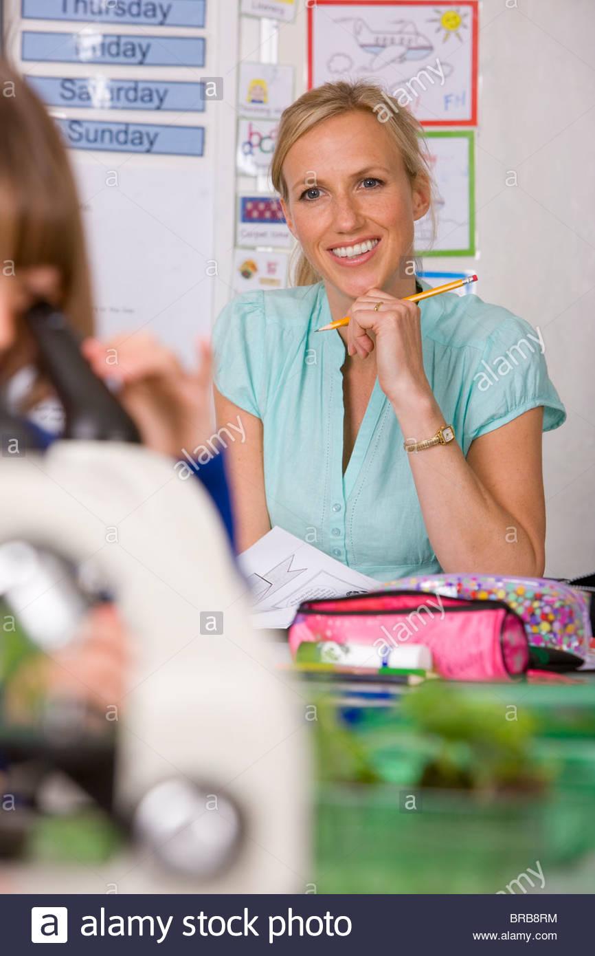 Smiling school teacher supervising children in classroom - Stock Image