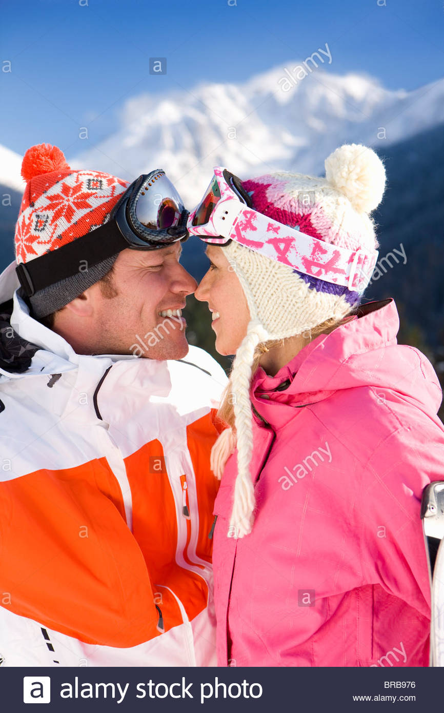 Couple in caps and coats about to kiss - Stock Image