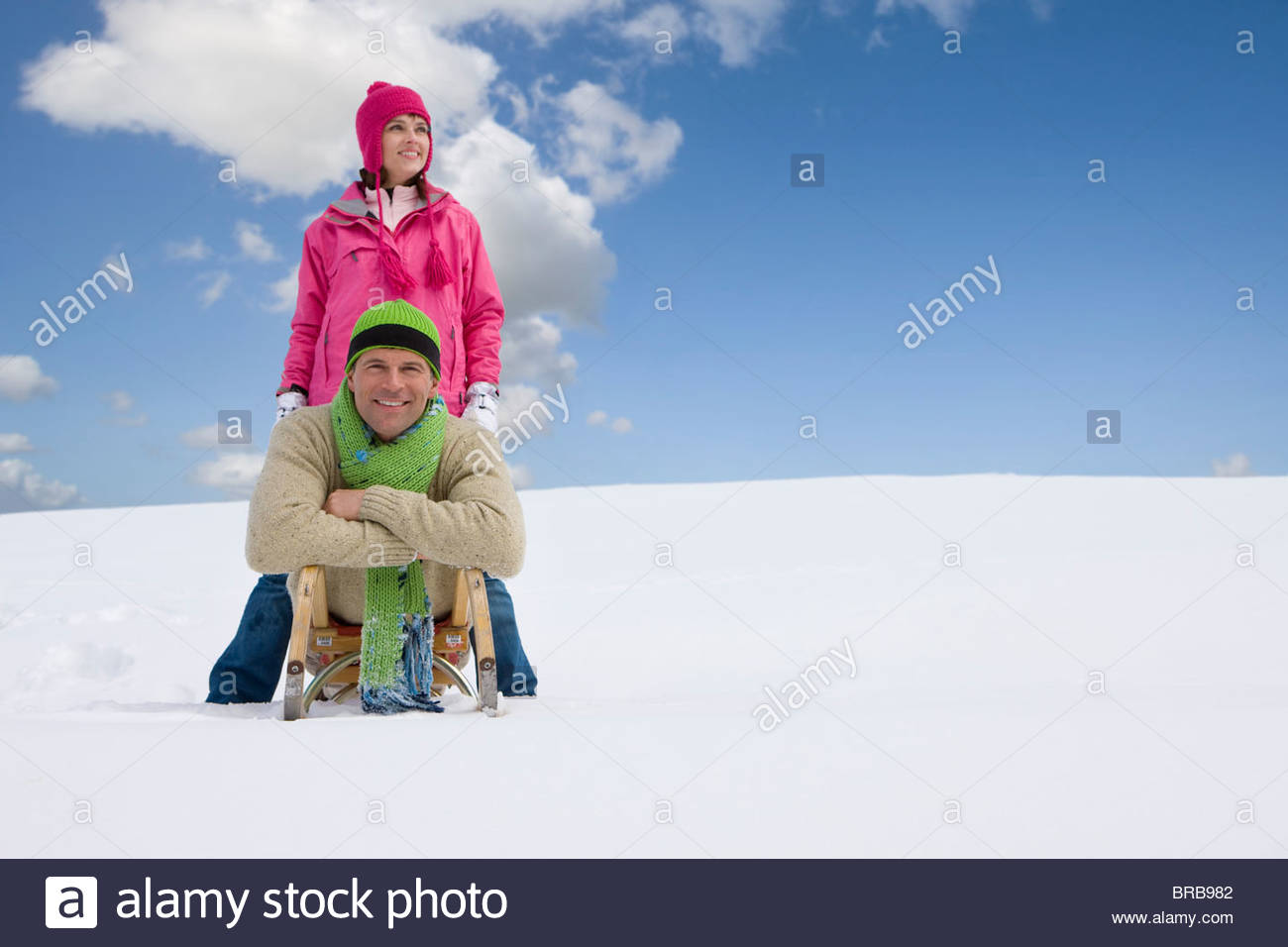 Man laying on sled with girlfriend standing in snow nearby - Stock Image