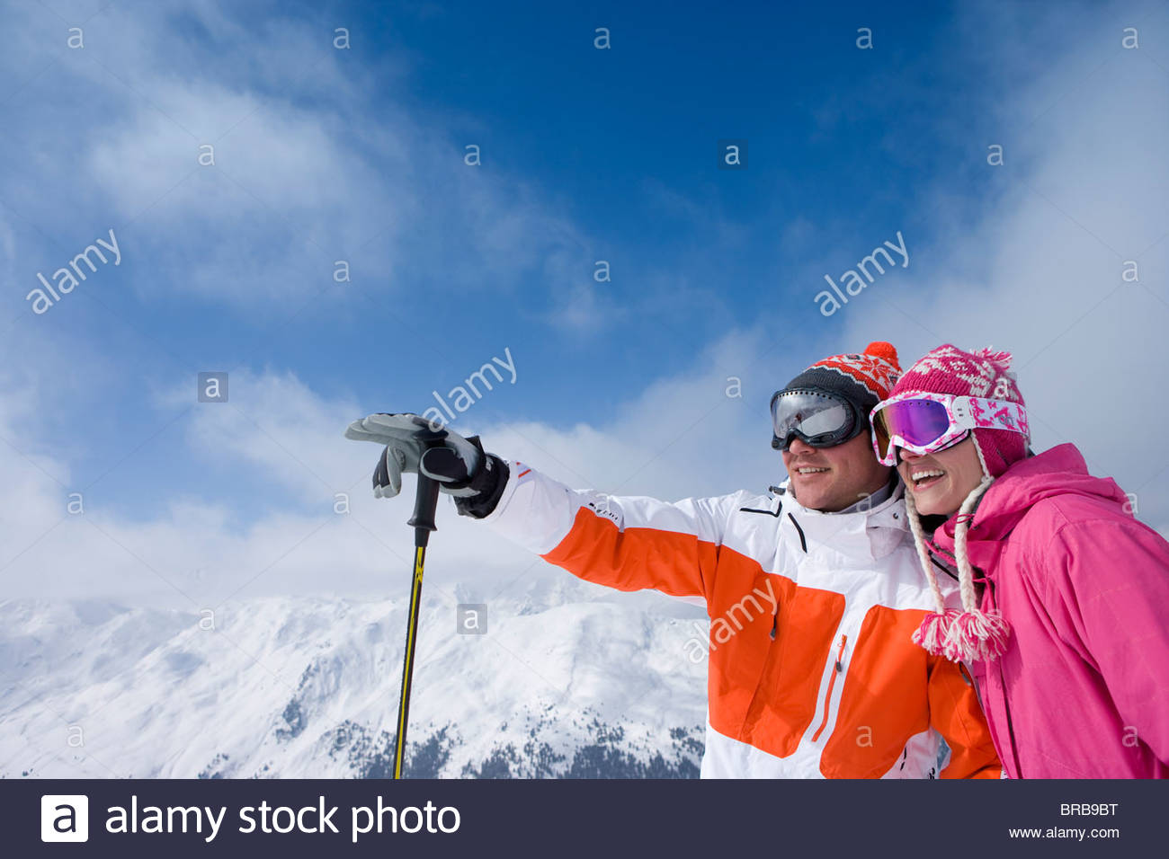 Skier on mountain top pointing out something for friend - Stock Image