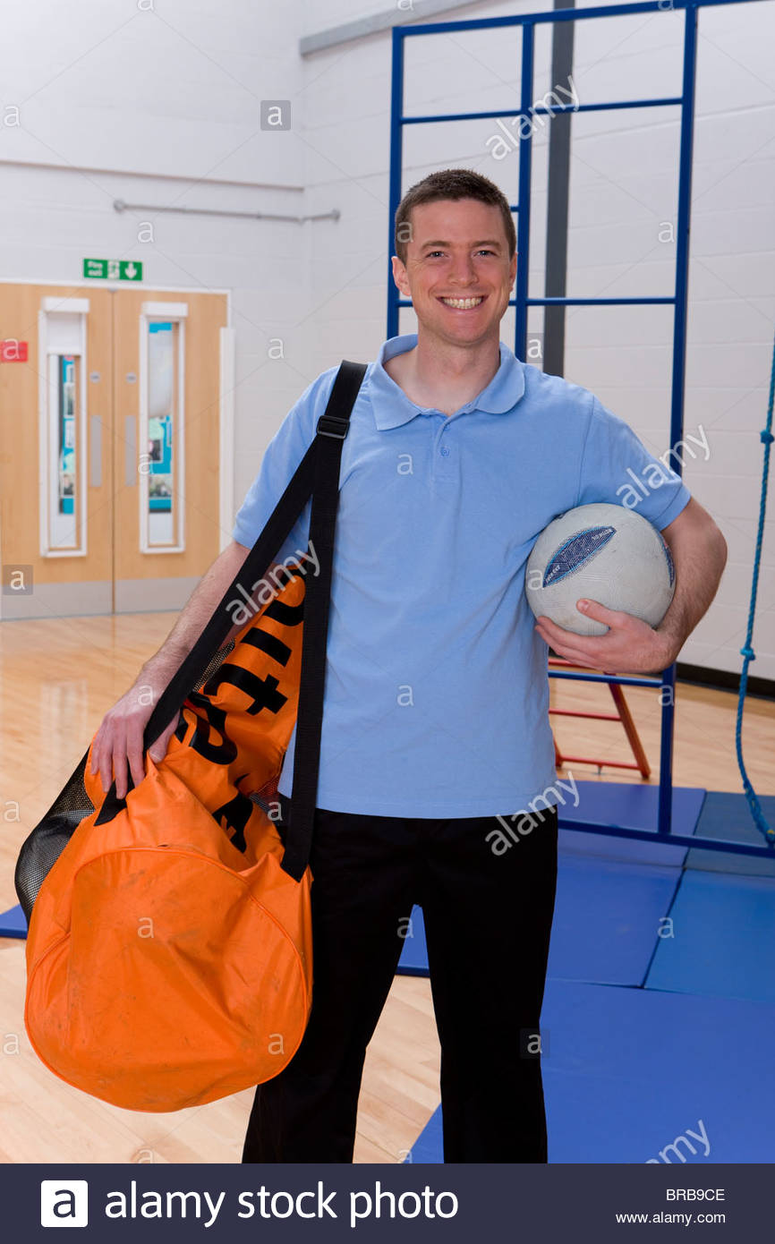 Gym teacher carrying bag of balls in school gymnasium - Stock Image