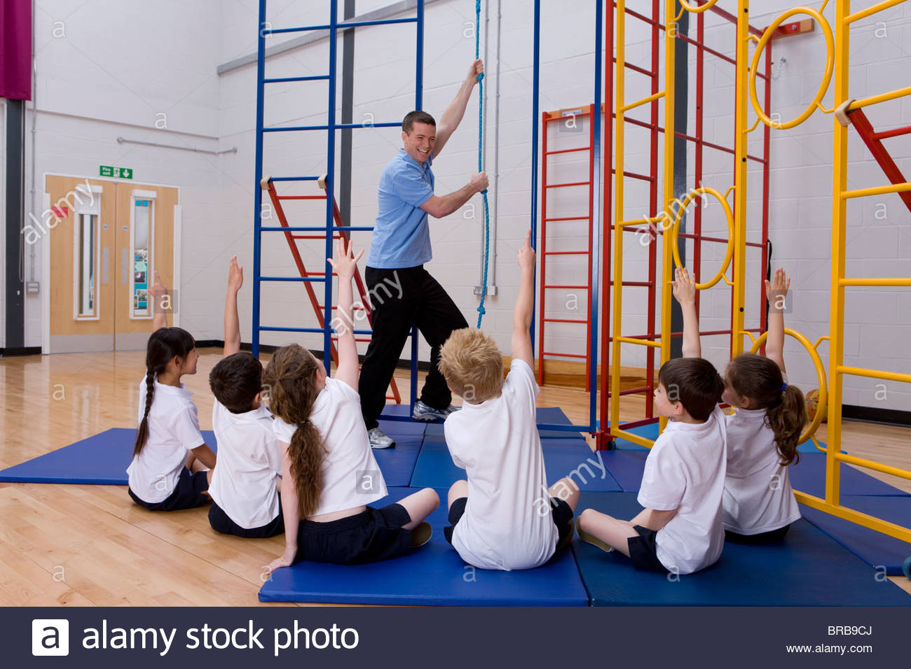 Gym teacher in school gymnasium with students