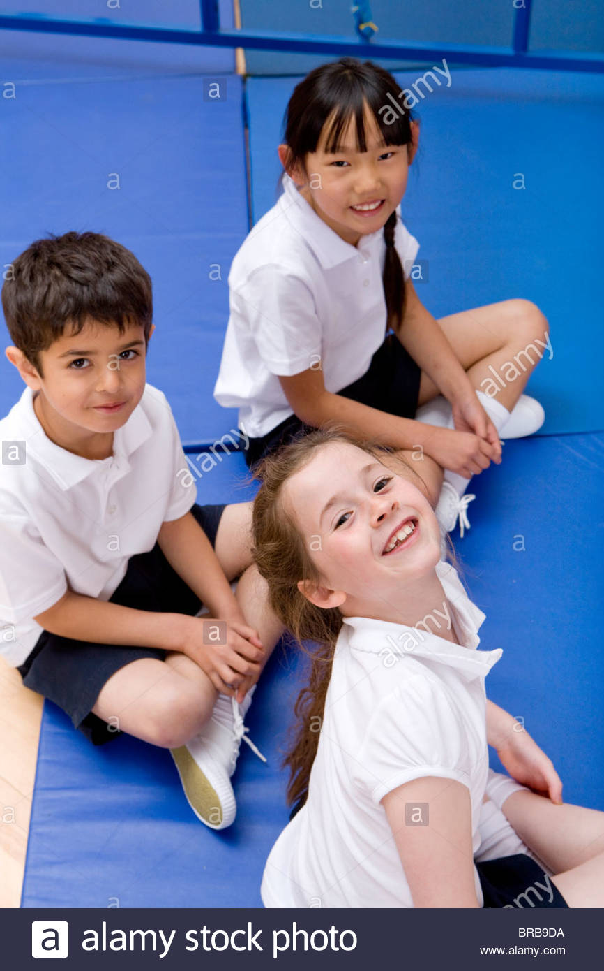 School children sitting in exercise mats in school - Stock Image