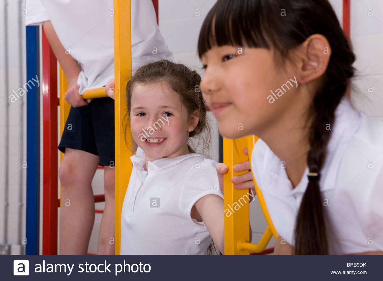 School children climbing gymnasium climbing equipment - Stock Image