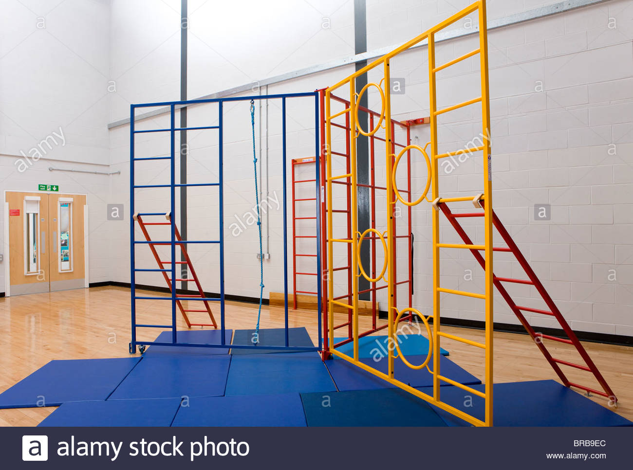 Climbing equipment and exercise mats in school gymnasium - Stock Image