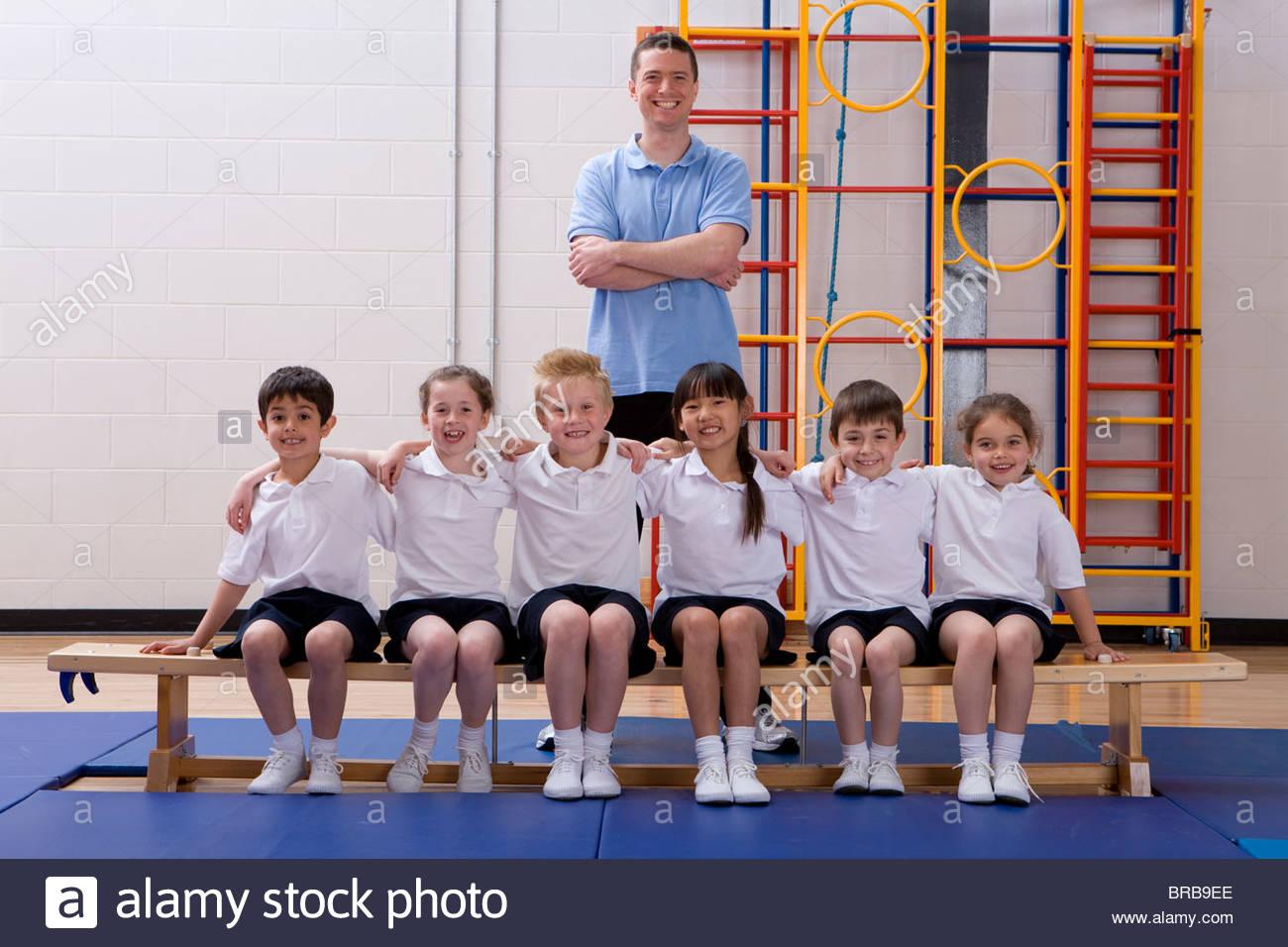 School children and teacher in school gymnasium - Stock Image