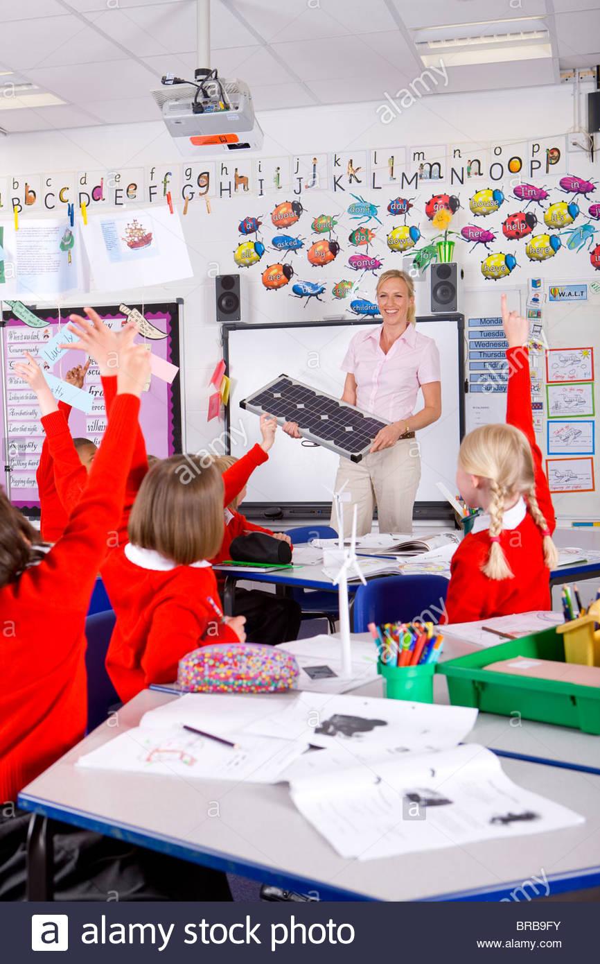 Teacher explaining solar panels to school children in classroom - Stock Image