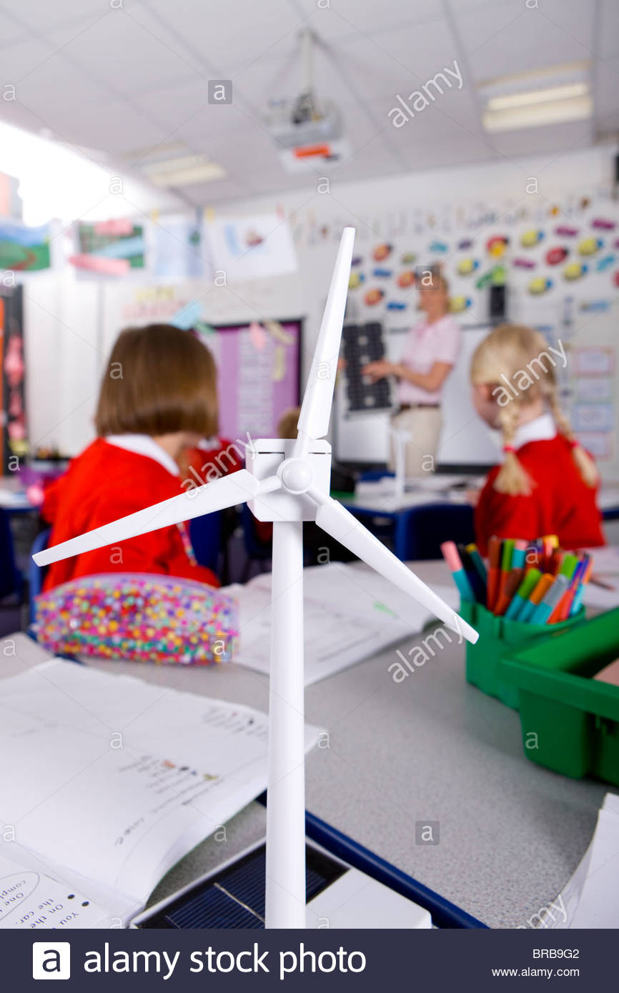 Teacher explaining solar panels to school children in classroom with wind turbine in foreground - Stock Image