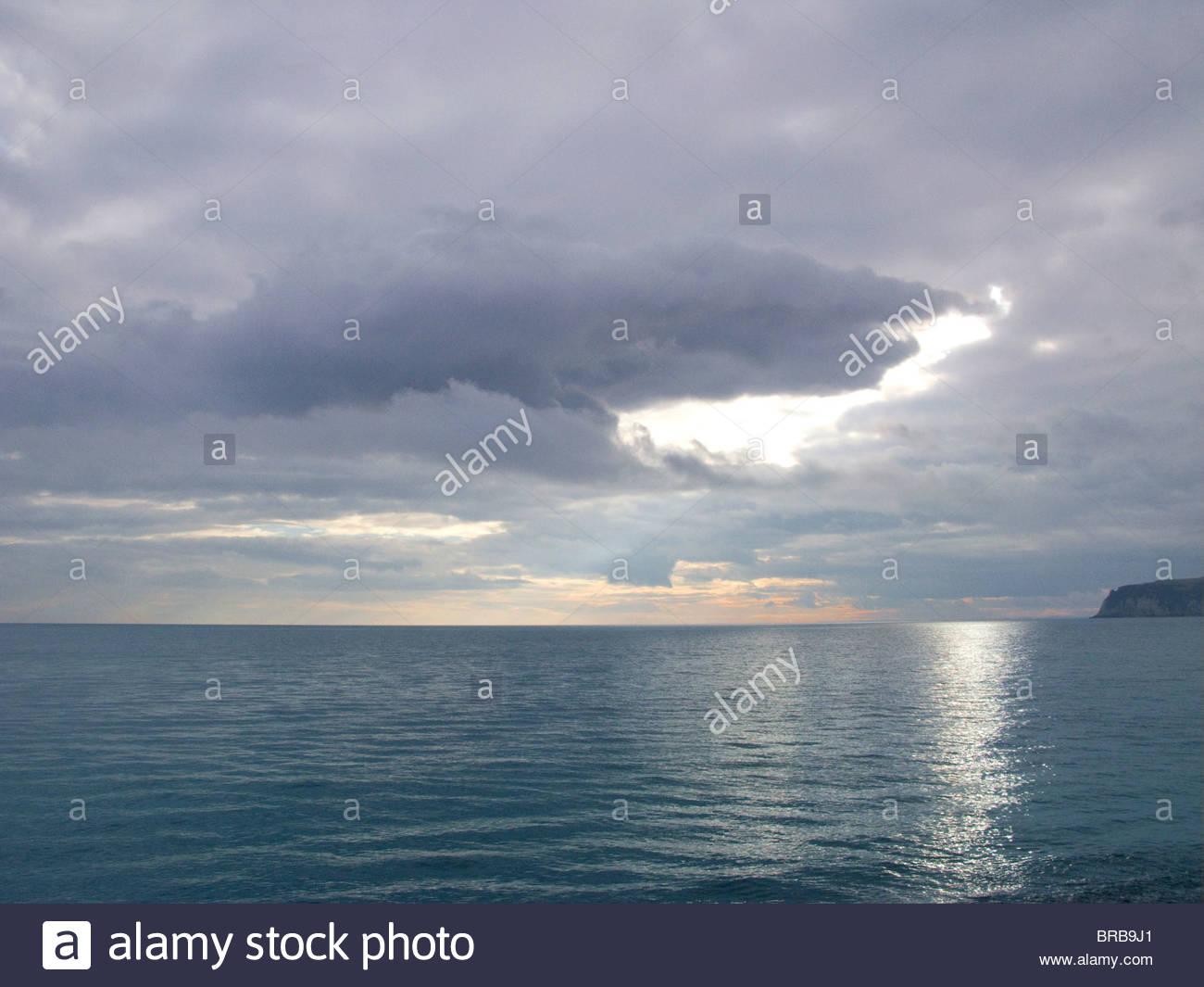 Overcast sky over tranquil ocean - Stock Image