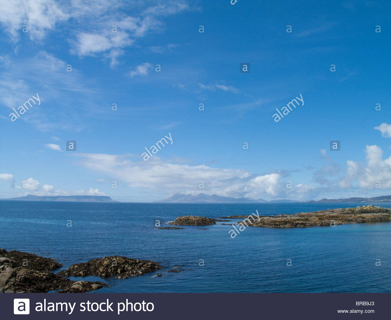 Blue sky over tranquil ocean with rocks protruding - Stock Image