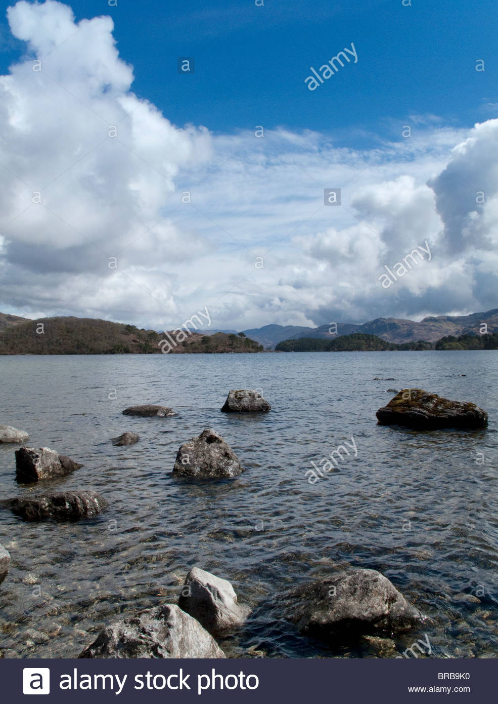 Rock protruding from ocean with land in background - Stock Image