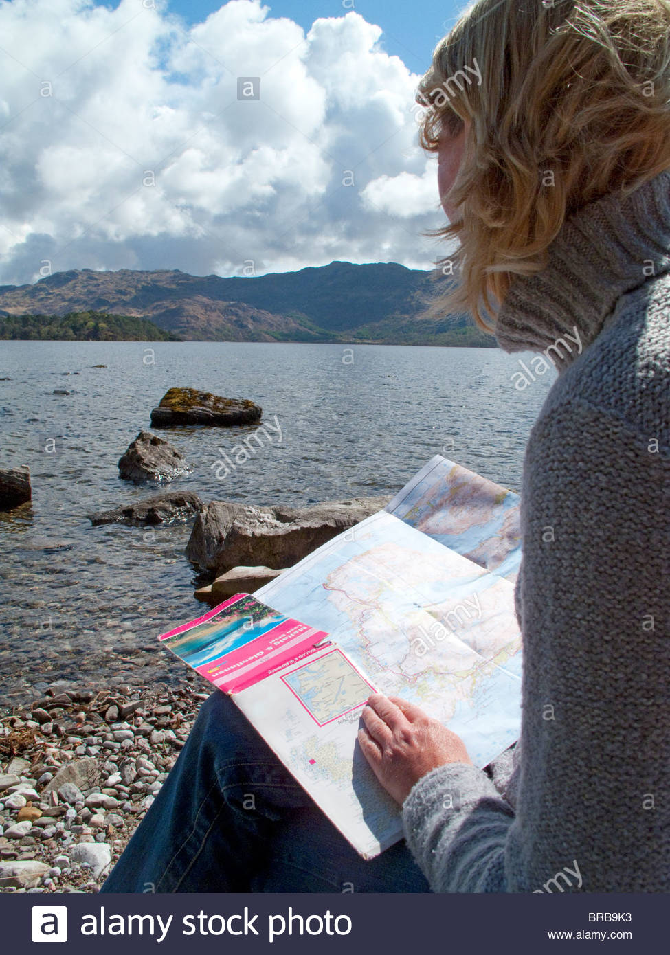 Woman looking at map and sitting rocky shore of lake - Stock Image