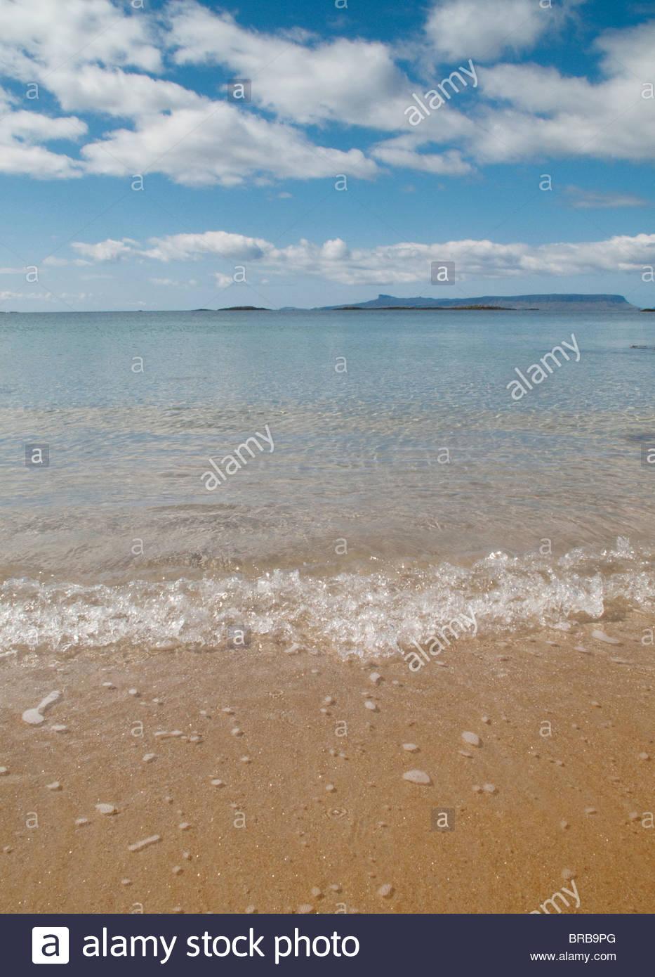 Ocean waves on beach under blue sky Stock Photo