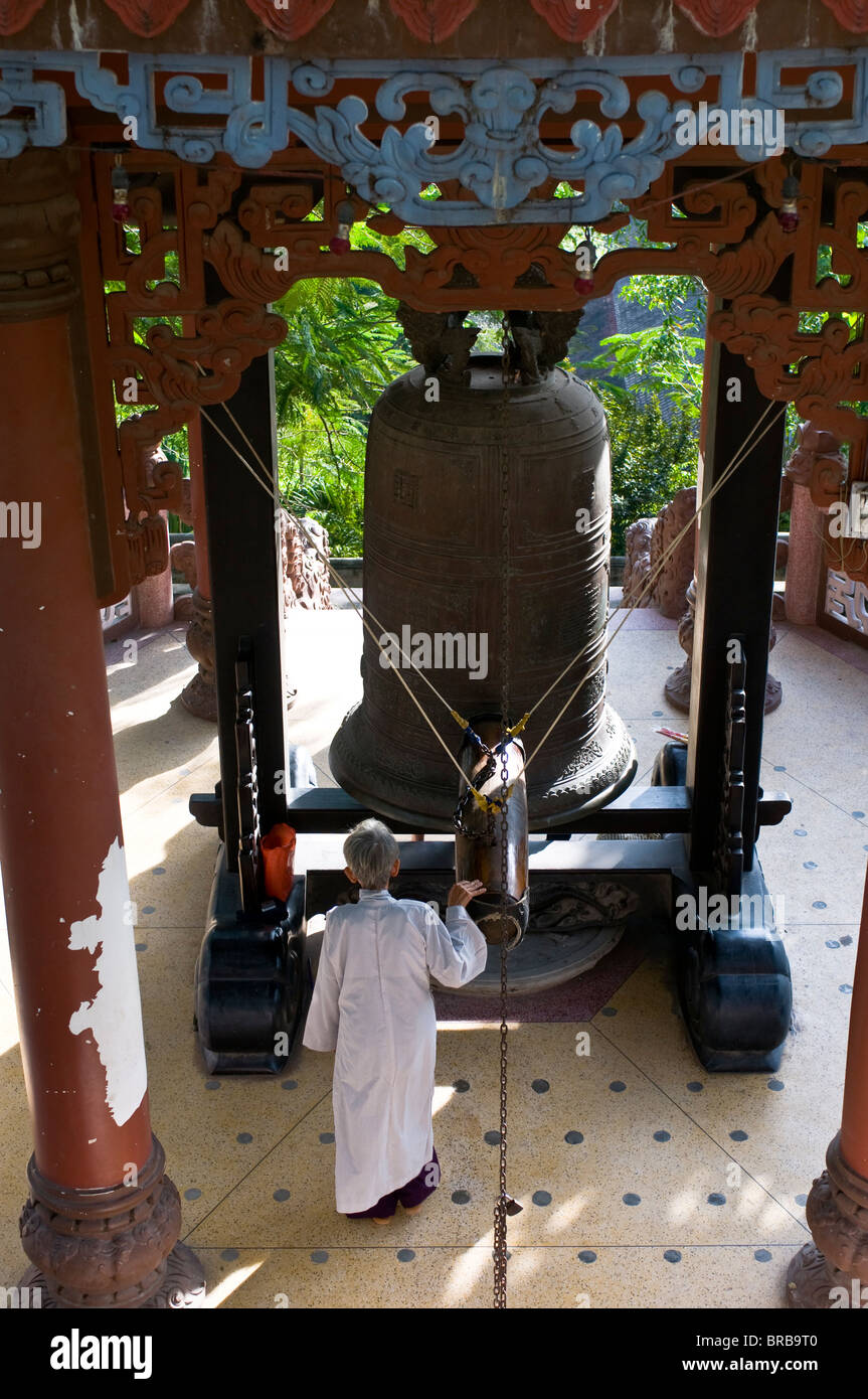 Nun ringing a giant bell, Long Son Pagoda, Vietnam, Indochina, Southeast Asia, Asia - Stock Image