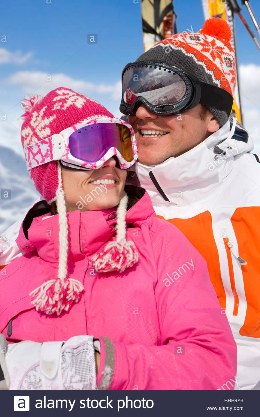 Smiling skiers in caps and goggles hugging - Stock Image