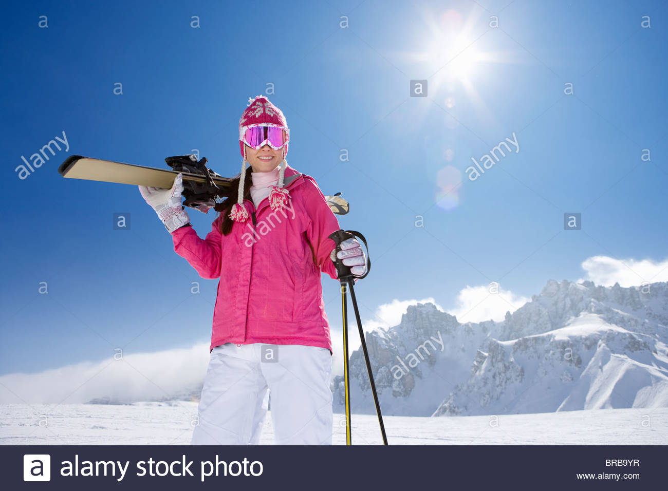 Skier carrying skis and standing on ski slope - Stock Image