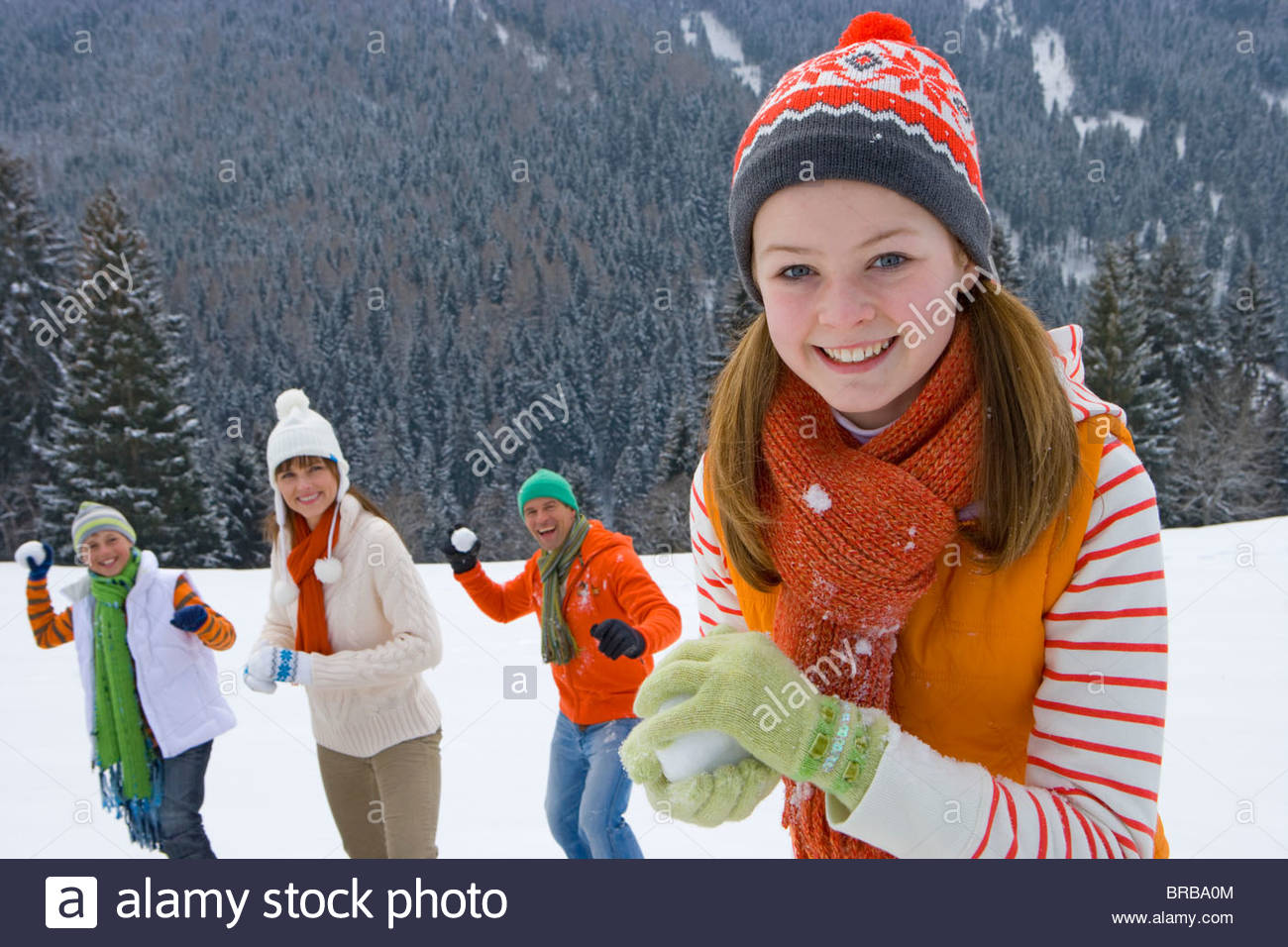 Smiling family having snowball fight in snow - Stock Image