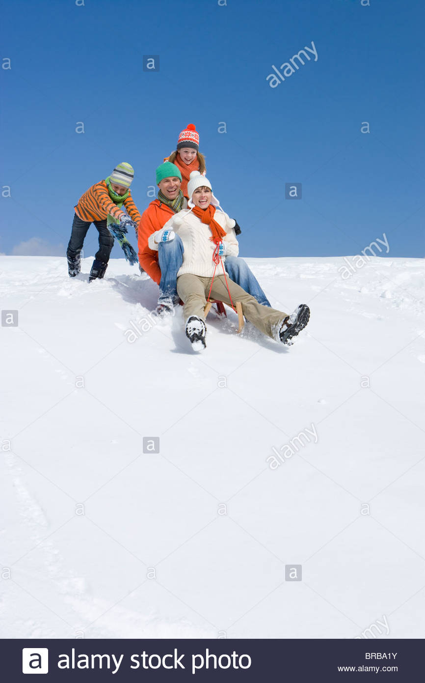 Children pushing parents downhill on sled on ski slope - Stock Image