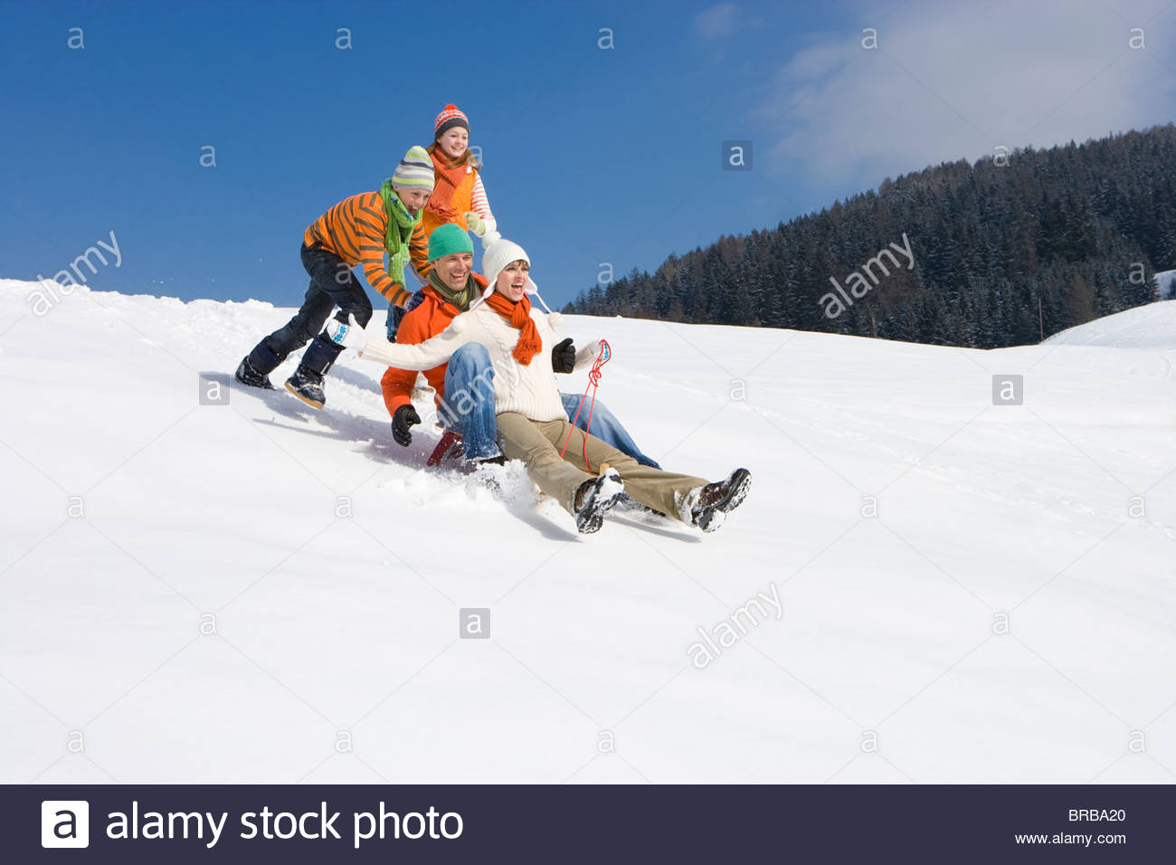 Children pushing parents downhill on sled on ski slope - Stock Image