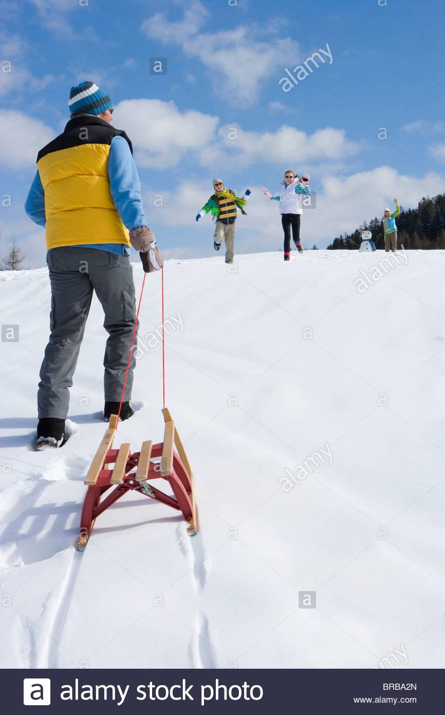 Man pulling sled up hill on ski slope - Stock Image