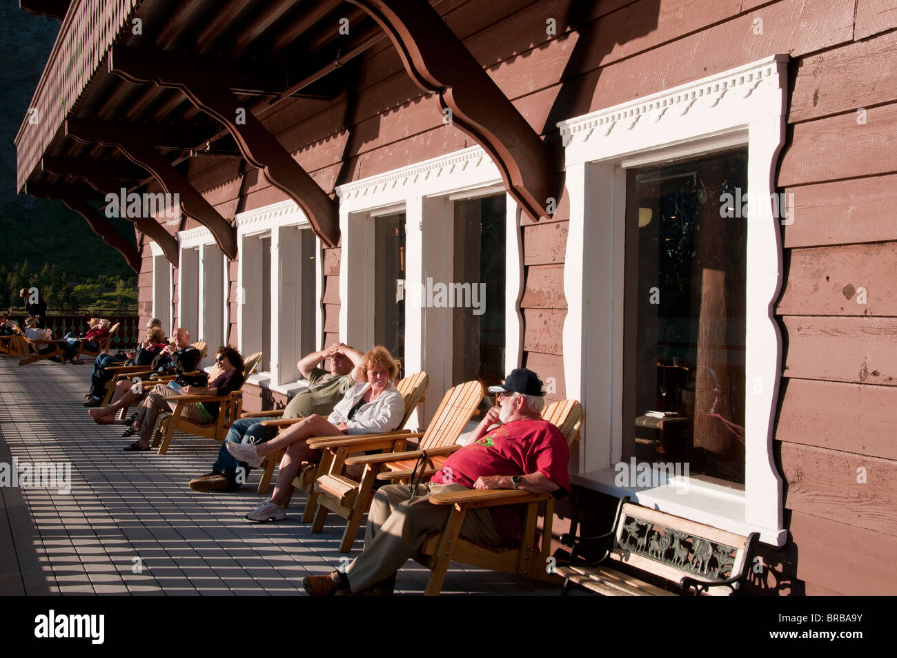 Folks relax and catch rays on the deck, Many Glaciers Hotel, Glacier National Park, Montana. Stock Photo