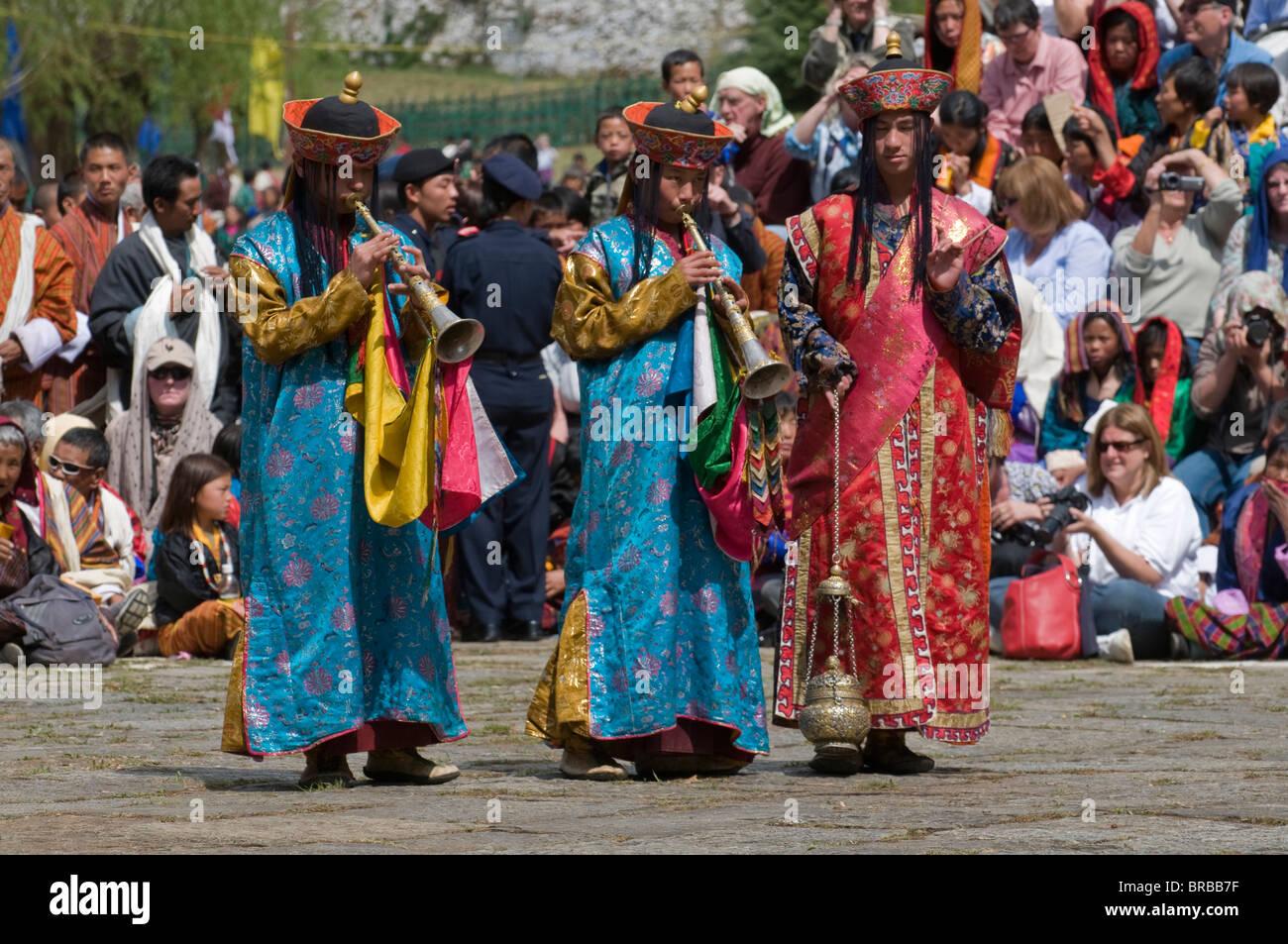 Buddhists playing the flute at religious festivity, Paro Tsechu, Paro, Bhutan - Stock Image