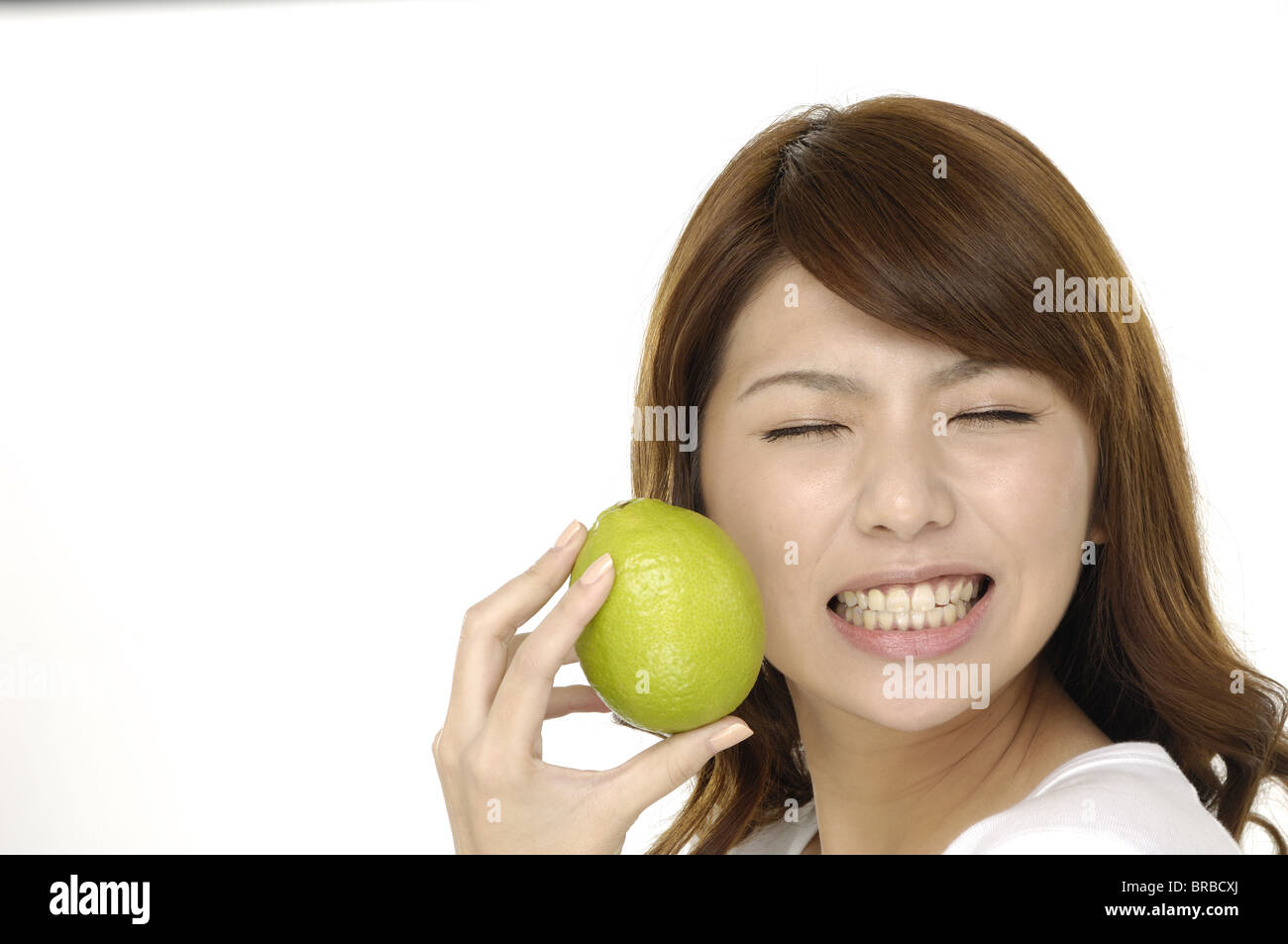 A woman with a lime. The sour flavor of the lime made her make a funny face Stock Photo