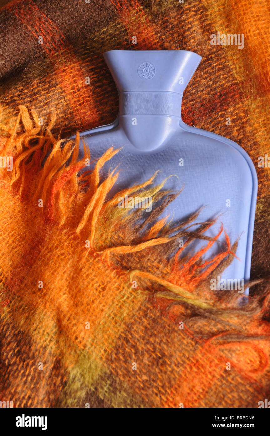 A blue hot water bottle partially covered by a red checkered woolen blanket with fringes. - Stock Image