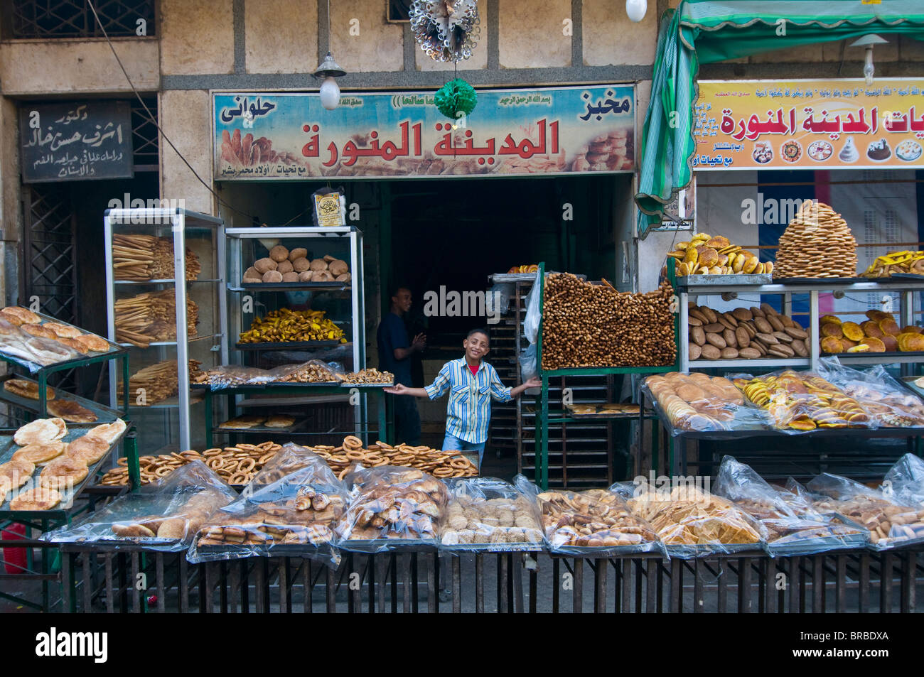 Young boy selling fresh bread in a bakery in the old part of Cairo, Egypt, North Africa - Stock Image
