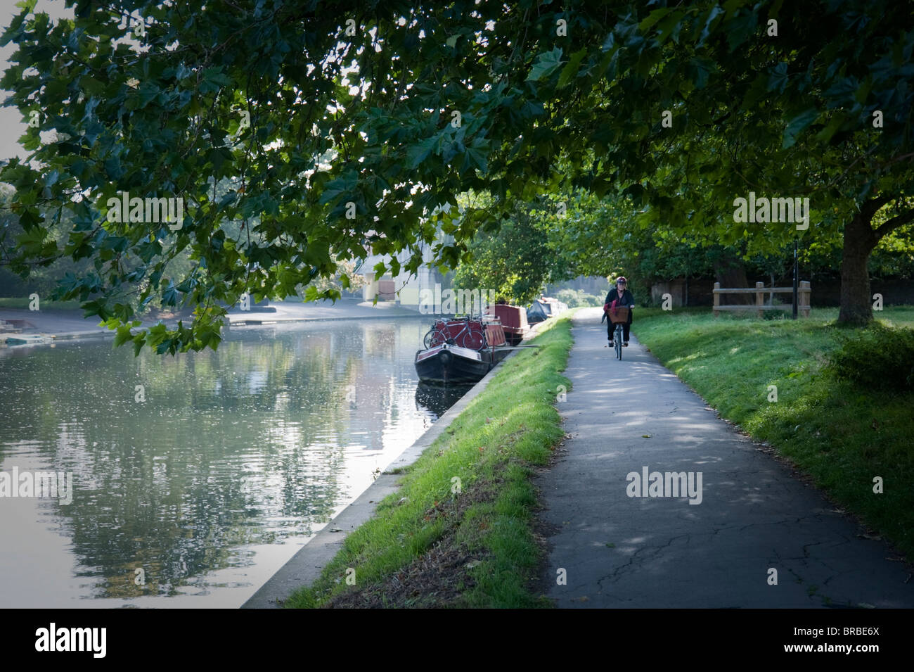 Lone cyclist on towpath along the River Cam in Cambridge, passing moored boats, in early morning autumn light. - Stock Image