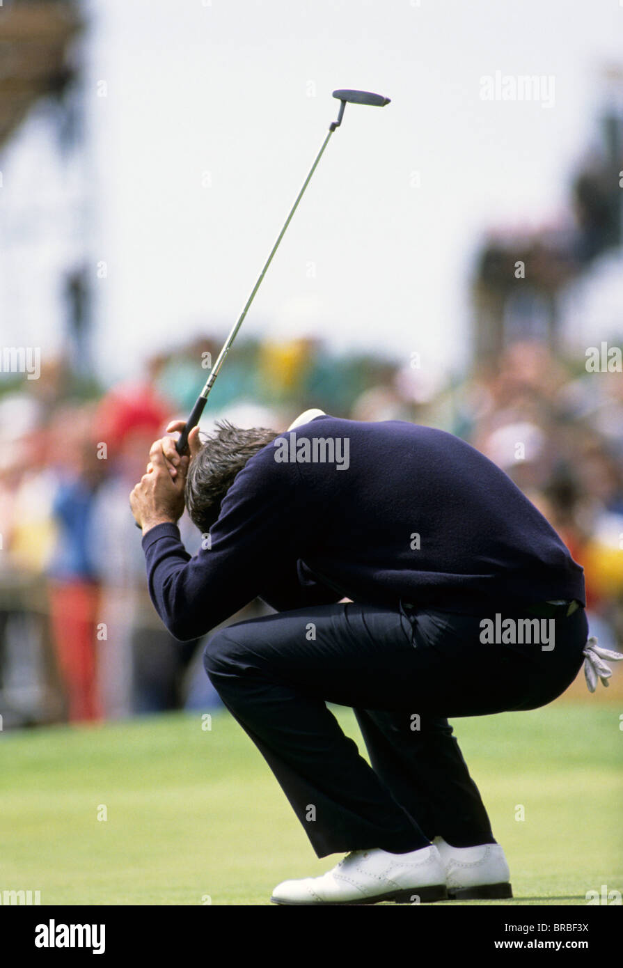 Golf player crouched on the green having missed his shot - Stock Image