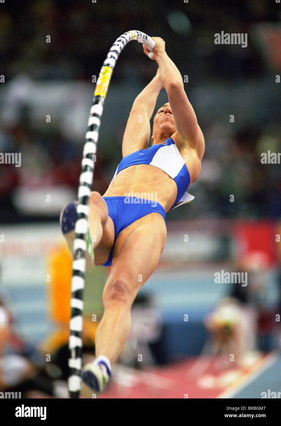 Female pole-vaulter bends pole as she launches herself at bar - Stock Image
