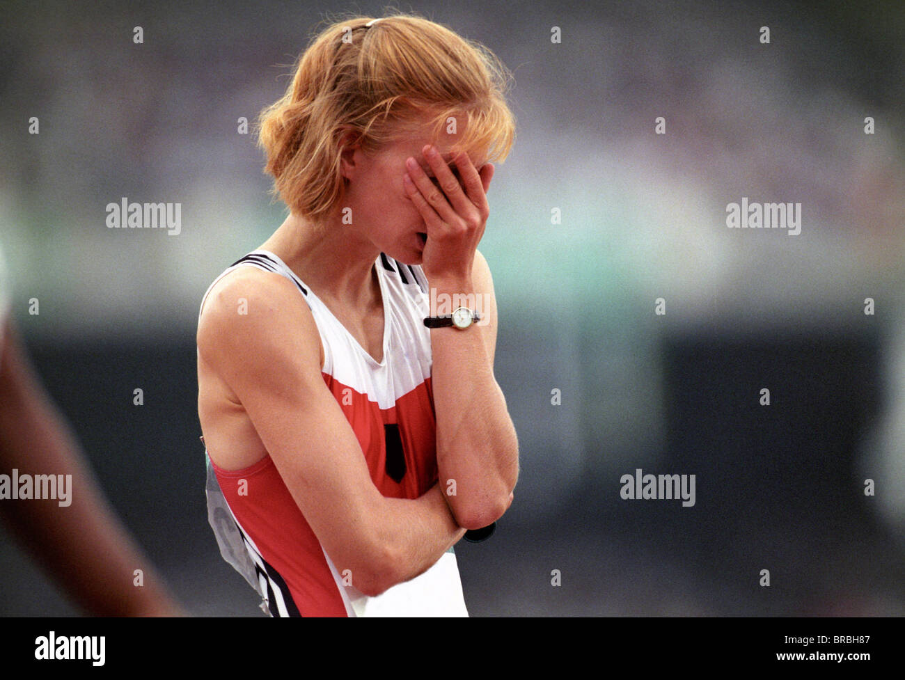Female athlete covers her face in disappoinment - Stock Image