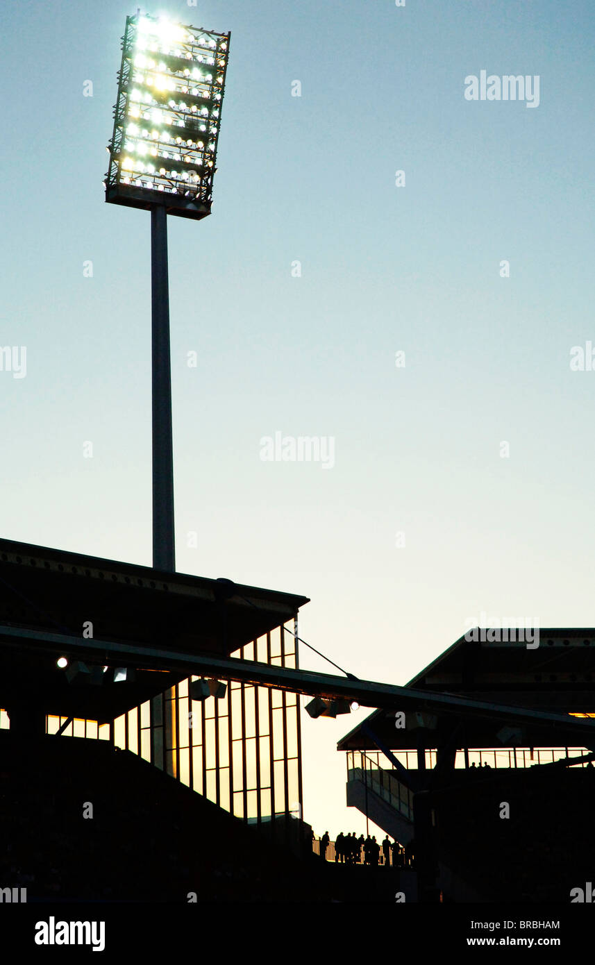 Floodlight at football stadium, silhouette of stand. - Stock Image